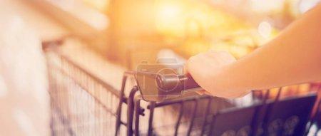 Photo pour Image recadrée de femme achats avec chariot dans la boutique - image libre de droit
