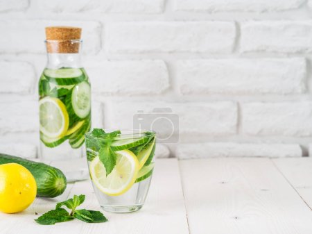 Photo for Infused detox water with cucumber, lemon and mint in glass and bottle on white table. Diet, healthy eating, weight loss concept. Copy space - Royalty Free Image