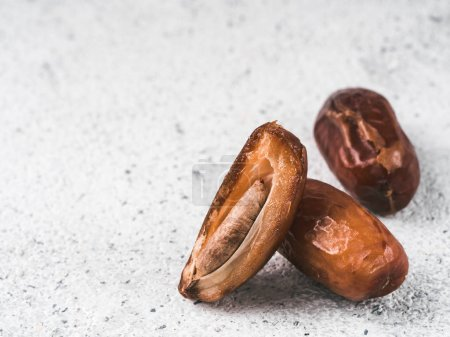 Photo for Sweet raw dates on gray cement background. Whole dates and half with bone date on grey concrete surface. Sugar free alternatives concept with space for text. Extreme close up view - Royalty Free Image