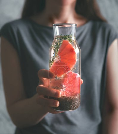 Photo for Woman hand with chia water. Glass bottle with chia detox water with grapefruit and thyme. Toned image. Dark or low key. Selective focus. Healthy eating, drinks, diet, detox and people concept - Royalty Free Image