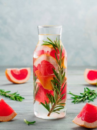 Photo for Infused detox water with grapefruit and rosemary in glass bottle on gray wooden table. diet healthy eating and weight loss concept, copy space for text - Royalty Free Image