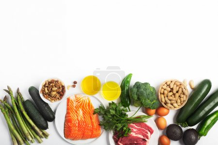 Photo for Ketogenic, keto diet, including vegetables, meat and fish, nuts and oil isolated on white background, horizontal with copy space - Royalty Free Image