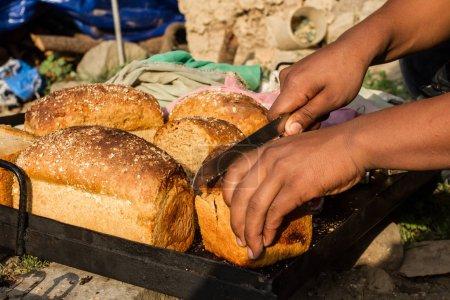 Street bakery. A man cuts fresh bread