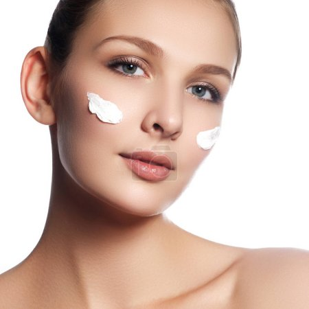 Photo for Beautiful face of young woman with cosmetic cream on a cheek. Skin care concept. Closeup portrait isolated on white. Close-up young beautiful face of girl applying moisturize cream - Royalty Free Image