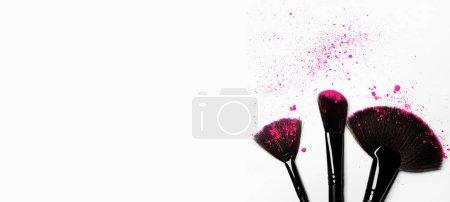 Photo pour Brosses de maquillage sur fond blanc avec de la poudre pigmentée colorée - image libre de droit