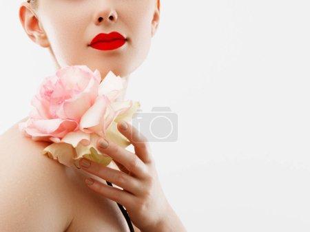 Photo pour Lèvres avec fleur. Gros plan belles lèvres femelles avec le maquillage brillant à lèvres rouge vif. Parfaire la peau propre, clair maquillage lèvres fraîches. Portrait du magnifique spa avec fleur de couleur tendre. Spa et cosmétiques - image libre de droit