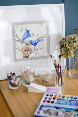 Photo for Art painting. inspiration and creative workspace concept. picture of birds. drawing creations. artist tools watercolors and stuff on the table - Royalty Free Image