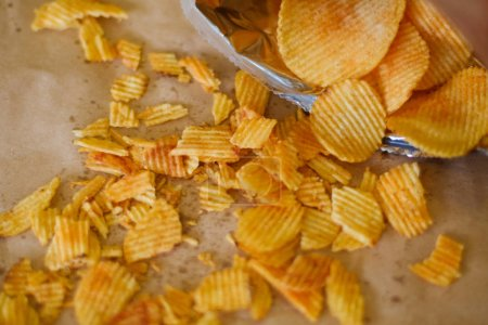 Photo for Crispy crunchy potato chips are a great party munchies. delicious food snack. waved rudged fried slices scattered on the surface - Royalty Free Image