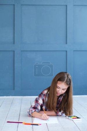 Photo pour Enfant dessinant loisirs. petite fille couchée sur le sol et créant une image avec des crayons . - image libre de droit
