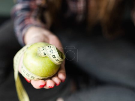 Photo for Healthy diet eating. weightloss and fit body. organic natural products for balanced nutrition. woman holding fresh apple with twisted measuring tape in hand. - Royalty Free Image