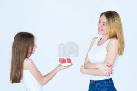 Photo pour Récompense pour la fête des mères. petite fille présente un cadeau à sa mère. amour et lien familial . - image libre de droit