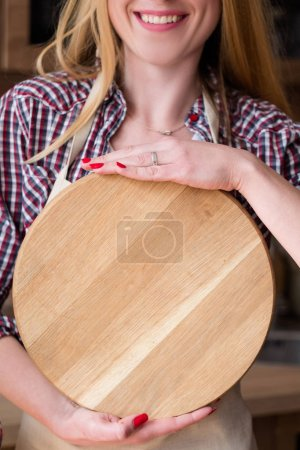 Photo for Smiling woman holding round wooden cutting board. kitchen utensils and food preparation. meal recipe. empty space for advertising. circle template - Royalty Free Image