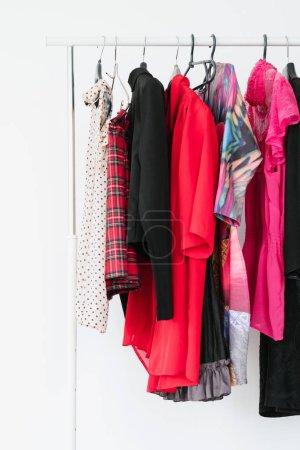 Foto de Guardarropa de la mujer con estilo. selección de colores de ropa de moda. Surtido de ropa de moda brillante sobre una rejilla - Imagen libre de derechos