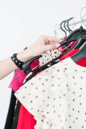 Photo for Fashion clothing shopping. woman hand choosing new apparel from a stylish clothes selection hanging on the rack. consumerism and female lifestyle - Royalty Free Image