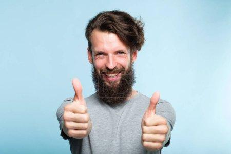 Photo pour Les pouces levés. Bon boulot. comme et concept d'approbation. homme barbu motivé enthousiaste montrant geste. casual hipster guy portrait sur fond bleu . - image libre de droit