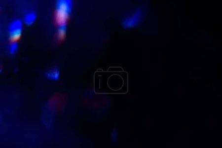 Foto de Destello de lente abstracta sobre fondo negro. luces azules defocused. que brilla intensamente difuminado color burst. telón de fondo del festivo de año nuevo. - Imagen libre de derechos