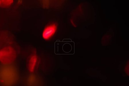 Photo for Abstract lens flare on black background. red defocused lights. glowing blurred color burst. festive new year backdrop. - Royalty Free Image