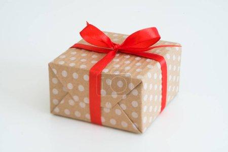 Foto de Regalo de año nuevo en caja de regalo envuelta en arte papel punteado y atado con un lazo de cinta roja. paquete sobre fondo blanco con copyspace. - Imagen libre de derechos