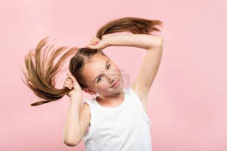 Photo pour Joyeux joyeuse sourire adolescente faisant des queues de cochon de ses cheveux. style de vie détendu sans soucis et comportement enfantin. portrait de jeune garçon aux cheveux brun mignon sur fond rose. - image libre de droit