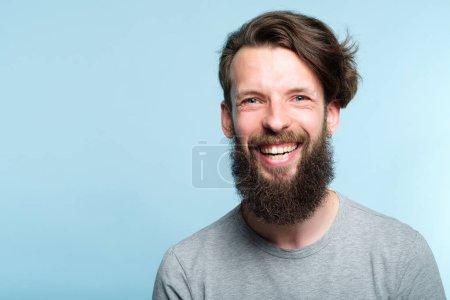 Foto de Expresión de la emoción. muy feliz alegre encantados de bits hombre con sonrisa radiante. joven guapo con barba retrato de guy en fondo azul - Imagen libre de derechos