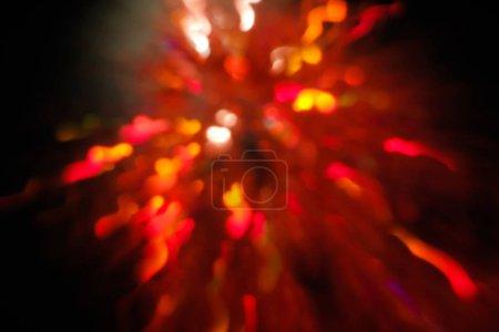 Foto de Destello de lente abstracta sobre fondo negro. rojo defocused luces bokeh. Bengala borrosa Navidad papel pintado una decoración. festivo brillante diseño de fuegos artificiales de año nuevo - Imagen libre de derechos