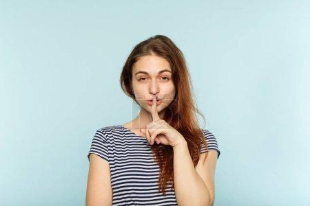 Photo pour Calme et silence. femme shushing le spectateur. portrait de jeune fille belle sur fond bleu. doigt sur les lèvres. - image libre de droit