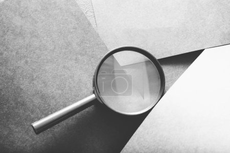 Photo for Magnifier on grey layered paper background. searching seeking looking recruiting and headhunting concept. - Royalty Free Image