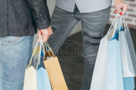 Photo for Shopping therapy and goods buying addiction. cropped shot of man and woman with multiple bags in hands. - Royalty Free Image