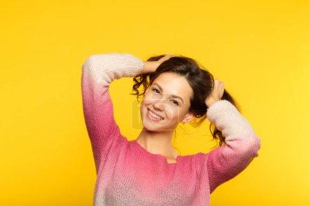 Photo pour Heureuse fille souriante joyeuse fabrication de queues de cochon de ses cheveux. style de vie détendu insouciante adolescence et comportement enfantin. portrait de la belle jeune femme aux cheveux bruns sur fond jaune. - image libre de droit