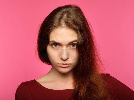 Photo pour Poupe regard perçant. Portrait d'une jeune femme sérieuse de féroce. expressions faciales émotionnelles. belle fille croisée sur fond rose. - image libre de droit