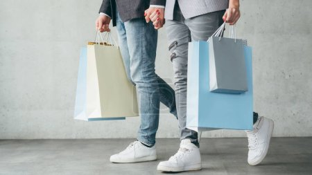 Photo for Shopping therapy for couples. cropped image of casual man and woman walking holding bags with goods. - Royalty Free Image