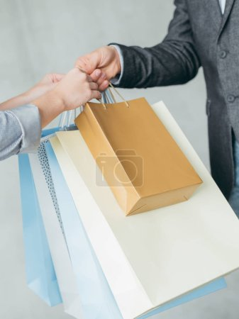 Photo for Online shopping therapy and store delivery. man hand passing bags with purchases to a female customer. - Royalty Free Image