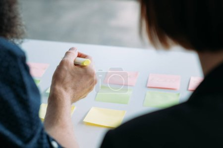 Photo for Corporate colleagues meeting. Coworking brainstorming with post it notes. Man and woman developing business strategy. - Royalty Free Image