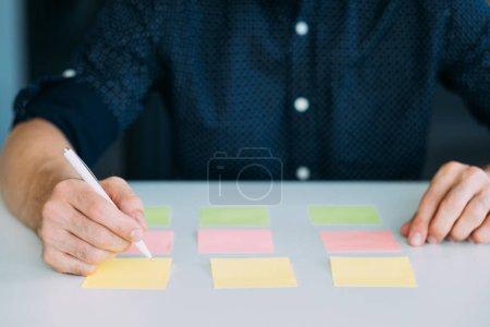 Photo pour Teamlead sur lieu de travail. Remue-méninges avec poster notes. Stratégie commerciale en développement exécutive homme. - image libre de droit