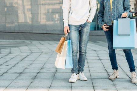 Photo pour Temps de shopping. Loisirs décontractés du couple urbain. Homme et femme avec des sacs en papier. Espace de copie pour la publicité . - image libre de droit