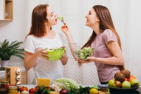 Photo for Healthy nutrition. Vegan lifestyle. Young females with salad bowls feeding each other. Fruit and vegetables assortment. - Royalty Free Image
