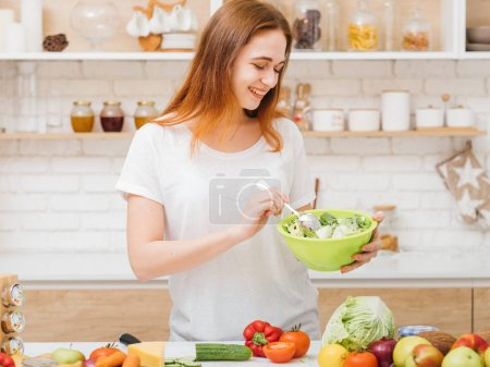 Photo for Organic nutrition. Health care. Female eating habit. Smiling young woman with bowl of fresh green salad. - Royalty Free Image
