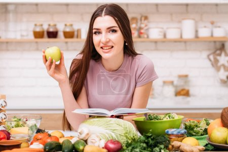 Photo for Healthy eating. Organic nutrition benefits. Young female with apple and book of vegetarian recipes. - Royalty Free Image