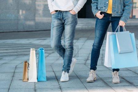 Photo pour Temps de shopping. Quelques loisirs décontractés. Homme et femme avec des sacs en papier. Jambes en jeans plan recadré . - image libre de droit