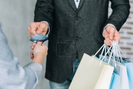 Photo for Shopping with credit card. Season store sale. Man with bags variety at checkout. - Royalty Free Image