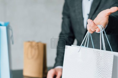 Photo for Shopping reward. Loyalty program. Checkout man presenting paper packet for regular customer. - Royalty Free Image