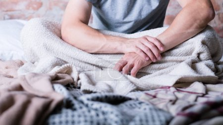 Photo for Morning again. Time to wake up. Man sitting in messy bed. Hands folded. Stress and insomnia. - Royalty Free Image