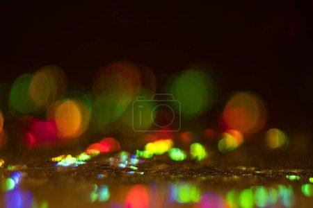 Foto de Círculos de borrosa bokeh multicolor sobre fondo oscuro. Resplandor de la llamarada Defocused lente. Diseño abstracto. - Imagen libre de derechos