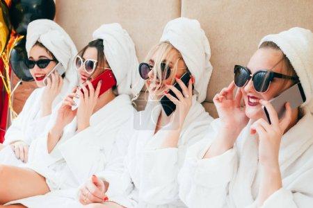 Cheerful spa girls talking on smartphones. Urban f...