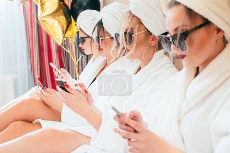 Photo pour Belle mode de vie des femmes. Des visages d'assurance. Smartphones dans les mains. Lunettes de soleil, peignoirs et turbans. Luxe . - image libre de droit