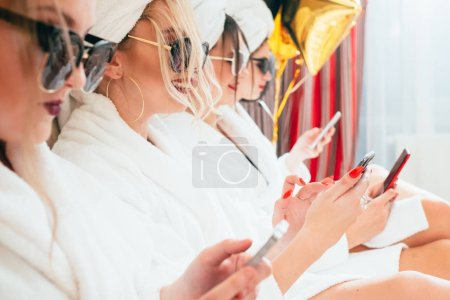 Photo pour Loisirs au spa. Temps de relaxation des femmes. Rangée de BFF en lunettes de soleil et peignoirs. Smartphones dans les mains . - image libre de droit