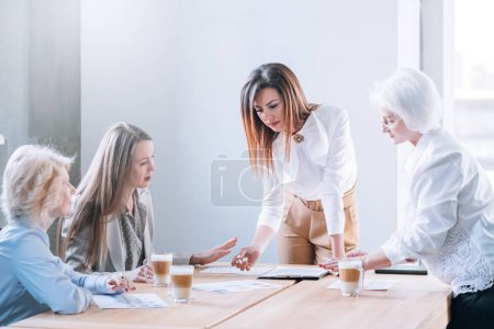 Photo for Business meeting. Project management. Young ambitious female team leader reviewing reports prepared by mature employees. - Royalty Free Image