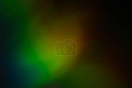 Foto de Blurred multicolor light reflection. Defocused lens flare glow. Dark abstract background. - Imagen libre de derechos