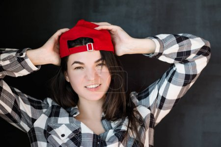 Photo for Young woman portrait. Carefree friendly millennial. Red cap casual clothes. Relaxed posture. Warm smile. Hands on head. - Royalty Free Image