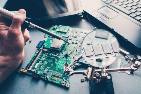Photo for Technician repairing pcb layout with soldering iron. Broken disassembled laptop. Electronic components. Computer analysis. - Royalty Free Image